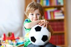 Kleiner blonder Vorschulkinderjunge mit Fußballfußball-Cupspiel des Balls aufpassendem im Fernsehen Stockbild