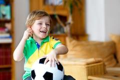 Kleiner blonder Vorschulkinderjunge mit Fußballfußball-Cupspiel des Balls aufpassendem im Fernsehen Stockfotos