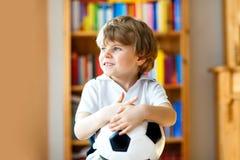 Kleiner blonder Vorschulkinderjunge mit Fußballfußball-Cupspiel des Balls aufpassendem im Fernsehen Lizenzfreies Stockbild