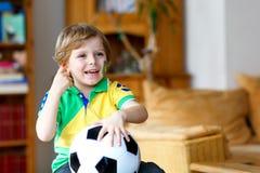 Kleiner blonder Vorschulkinderjunge mit Fußballfußball-Cupspiel des Balls aufpassendem im Fernsehen Lizenzfreie Stockbilder