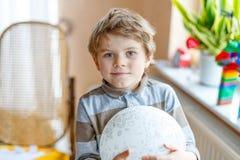 Kleiner blonder Vorschulkinderjunge mit Luftballonball Stockbild