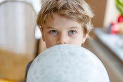 Kleiner blonder Vorschulkinderjunge mit Luftballonball Stockbilder