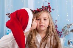 Kleiner Bruder, einen Kuss gebend seiner Schwester, Weihnachtskonzept Lizenzfreie Stockfotos