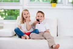 Kleiner Bruder und Schwester, die fernsieht Stockfotografie