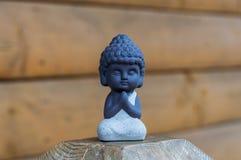 Kleiner Buddha, der keramische Statue betet Buddhismus, Yoga, Meditationskonzept stockfoto