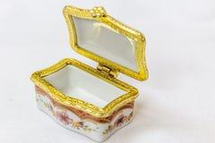 Kleiner bunter Schmuckkasten mit Gold flocht Falz in einem weißen Hintergrund Makro mit extrem flacher Schärfentiefe lizenzfreies stockbild