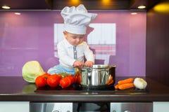 Kleiner Chef, der in der Küche kocht Stockfotografie