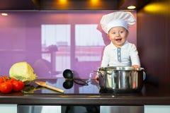 Kleiner Chef, der in der Küche kocht Stockbilder