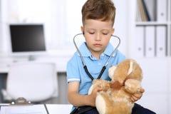 Kleiner Doktor, der einen ntoy Bärnpatienten durch Stethoskop überprüft Stockbilder