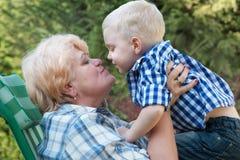 Kleiner Enkel, der die Großmutter sitzt in ihren Armen umarmt Leichte Küsse Familienurlaub draußen stockbild