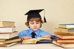 Kleiner ernster Junge im akademischen Hut alte Bücher lesend Stockbilder