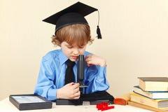 Kleiner ernster Junge im akademischen Hut, der durch Mikroskop seinem Schreibtisch betrachtet Stockfoto