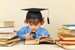 Kleiner ernster Junge im akademischen Hutablesen alte Bücher mit Lupe Stockbild