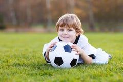 Kleiner Fanjunge an der allgemeinen Betrachtung des Fußballs oder des Fußballspiels stockfoto