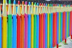 Kleiner farbiger dekorativer Zaun in Form von Bleistiften entlang der Straße Stockfotos