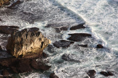 Kleiner Felsen auf Bank vom Indischen Ozean, von Wellen und von weißer Brandung Uluwat Stockfoto