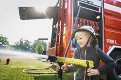 Kleiner Feuerwehrmann, der firehose Düse und Spritzwasser hält stockbild