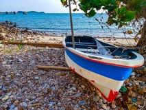 Kleiner Fiberglasbootsgebrauch für die Fischerei oder das Segeln des Sports auf dem Felsenstrand lizenzfreies stockfoto