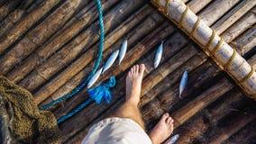 Kleiner Fisch-Fang auf Bambusfloss stockfoto