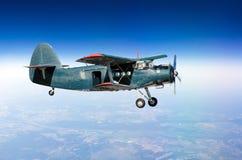 Kleiner Flugzeugturboprop-triebwerk Doppeldecker an der großen Höhe im Himmel über dem Boden mit einer offenen Tür Lizenzfreie Stockfotografie