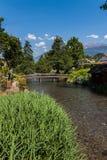 Kleiner Fluss mit Fußgängerbrücke in einem grünen Park mit blauem Himmel Stockfotografie