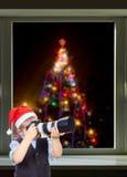 Kleiner Fotograf auf dem Hintergrund des schönen Weihnachtsbaums außerhalb des Fensters Lizenzfreie Stockfotos