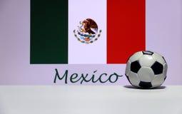 Kleiner Fußball auf dem weißen Boden und mexikanischen der Nationsflagge mit dem Text von Mexiko-Hintergrund Stockfotos