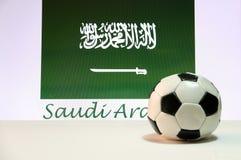Kleiner Fußball auf dem weißen Boden und saudi-arabischen der Nationsflagge mit dem Text von Saudi-Arabien Hintergrund lizenzfreie stockbilder