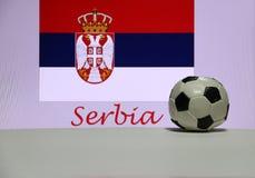 Kleiner Fußball auf der weißen Boden- und Serbenationsflagge mit dem Text von Serbien-Hintergrund Stockbilder