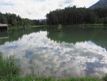 Kleiner Gebirgssee mit Reflexionen von Wolken Stockfotos