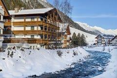 Kleiner Gebirgsstrom in Tirol-Alpen Holzhaus nahe Gebirgsfluss wird durch Schnee bedeckt lizenzfreie stockfotos