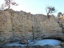 Kleiner gefrorener Teich unter Klippe stockbild