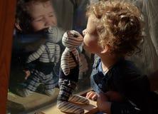 Kleiner gelockter blonder Junge, der mit abgestreifter Spielzeugkatze nahe spielt lizenzfreie stockfotos