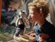 Kleiner gelockter blonder Junge, der mit abgestreifter Spielzeugkatze nahe spielt lizenzfreies stockbild