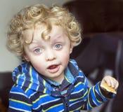 Kleiner gelockter blonder Junge mit einem Keks Stockfoto