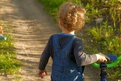 Kleiner gelockter blonder Junge mit wenigem Fahrrad im Freien Stockbilder