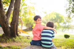 Kleiner Geschwisterjunge, der zusammen im Park im Freien sitzt Lizenzfreies Stockfoto