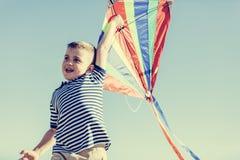 Kleiner glücklicher Junge, der mit einem bunten Drachen spielt Lizenzfreie Stockbilder
