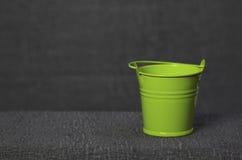 Kleiner grüner Eimer auf grauem Hintergrund Lizenzfreie Stockfotos
