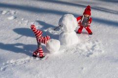 Kleiner hölzerner Mann zwei in der Szene des Errichtens eines Schneemannes unter Th Stockfotografie