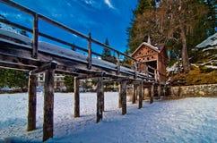 Kleiner hölzerner Pier auf Gebirgssee mit blauem Himmel und schneebedecktem Berg Lizenzfreie Stockfotografie