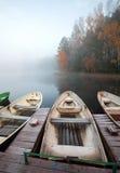 Kleiner hölzerner Pier mit Rowboats auf ruhigem See Stockbild