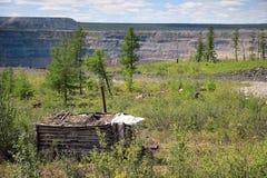 Kleiner hölzerner Schutz am Rand des offenen Bergwerkes Stockbild