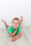 Kleiner hübscher Junge mit den blauen Augen, die auf dem Boden liegen Lizenzfreie Stockfotografie