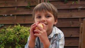 Kleiner hübscher Junge mit einem Apfel stock video