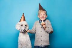 Kleiner hübscher Junge mit Hund feiern Geburtstag Freundschaft Liebe Kuchen mit Kerze Studioporträt über blauem Hintergrund stockfotografie