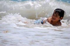 Kleiner hispanischer Junge, der in den Ozeanwellen spielt lizenzfreie stockbilder
