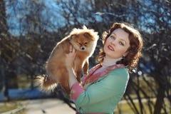 Kleiner Hund und recht rotes behaartes Frauenspielen im Freien Lizenzfreie Stockfotografie