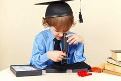 Kleiner intelligenter Junge im akademischen Hut, der durch Mikroskop seinem Schreibtisch betrachtet Stockbilder