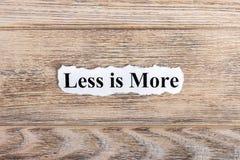 kleiner ist mehr Text auf Papier Wort ist weniger mehr auf heftigem Papier Figürchen, die auf dem Recht und dem Rest auf einem Stockfoto